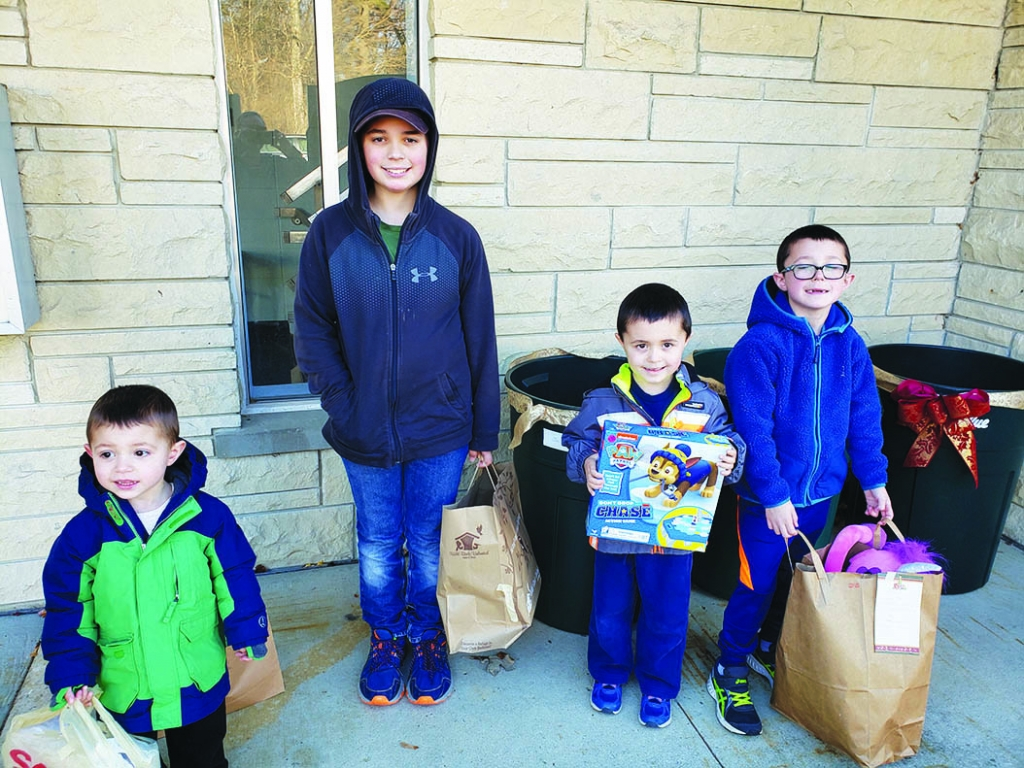 Sauk Prairie Earthling 4-H members Eric, Evan, Ian, and Owen Louis deliver toys to the Help Excite Little People (H.E.L.P) toy drive at the First...