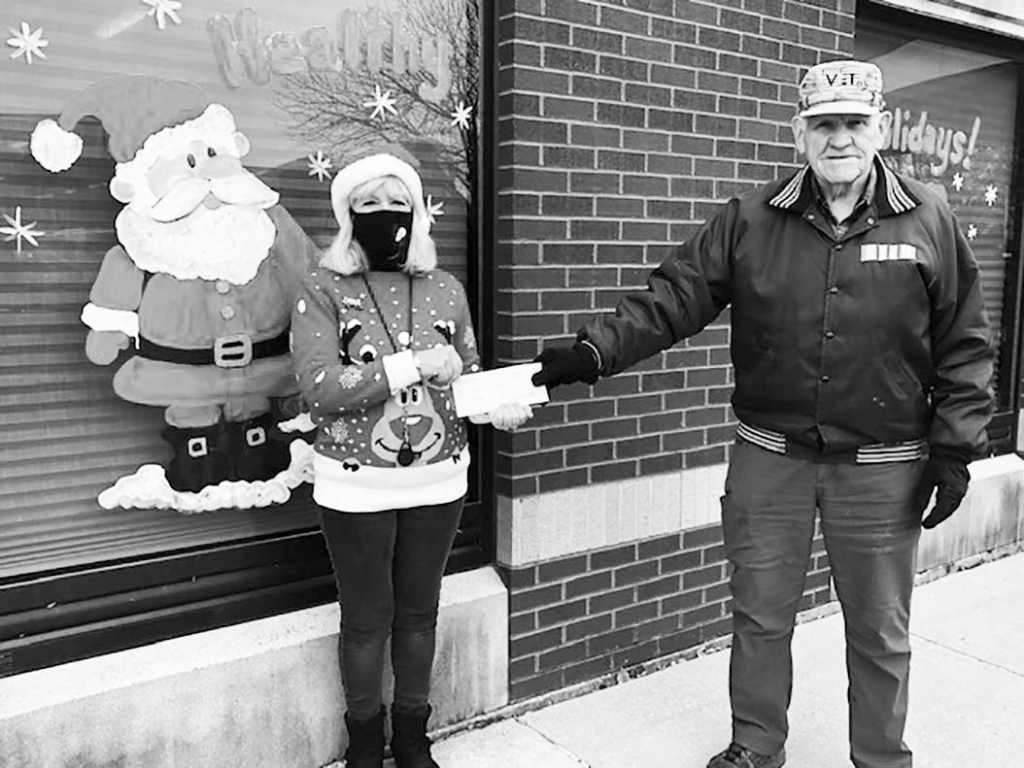 Diane Shaw, left, representing the Bank of Prairie du Sac, presented a check for $1000 to SP Optimist President, Bart Mauch, right, outside the bank...